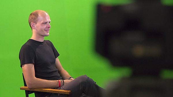 Man being interviewed in front of a green screen