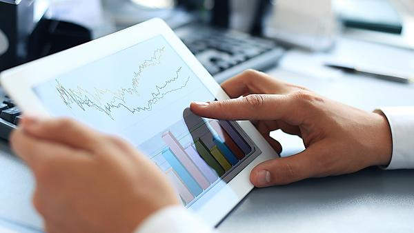 Business person analysing financial statistics displayed on the tablet screen, courtesy of Shutterstock