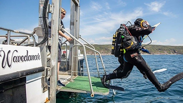 <p>Student divers stride entry from the DSV Wavedancer</p>