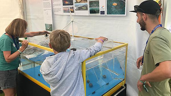 Deborah and Kieran using the tank to explain oscillating water columns - a type of wave energy converter that harnesses energy from the movement of seawater.