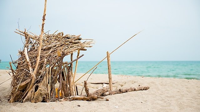 <p>A Robinson Crusoe refugee handmade shelter by the sea.</p>