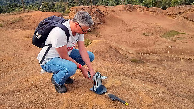 <p>Dr Andrew Turner conducting an XRF survey at a car park to the north of the site (Credit Charlotte Braungardt)<br></p>