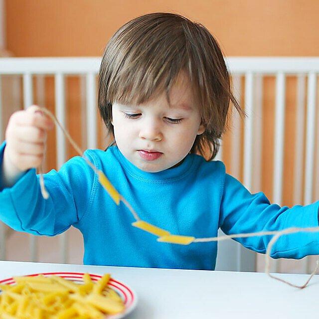 <p>Child making pasta jewelry</p>