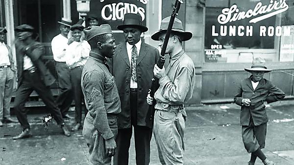 <p>A member of the state militia faces off against an African-American veteran during the 1919 Chicago Race Riot. July 27, 1919. Photograph - Chicago Tribune <br></p>