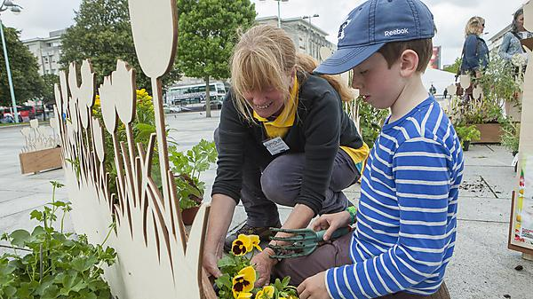 Adult volunteer planting flowers with a child, as part of the Plymouth in Bloom project