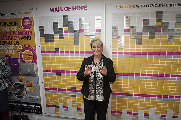 Irene Thomson, who has led the fundraising at Sainsbury, places a tile on the Wall of Hope