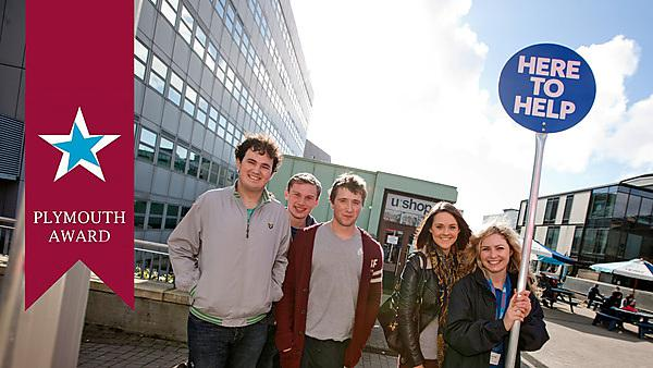 Students on campus with Plymouth Award banner