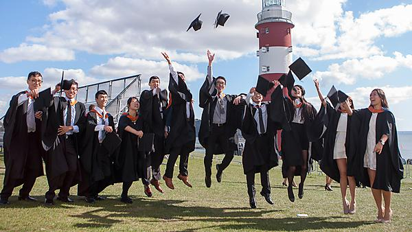 Hong Kong IVE students celebrating at their graduation ceremony on Plymouth Hoe