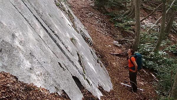 Dr Zoë Mildon   standing at the base of an active fault scarp, Maiella National Park, Abruzzo