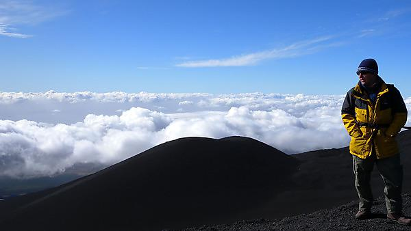 Research student stood on Mount Etna, on a geology field trip.