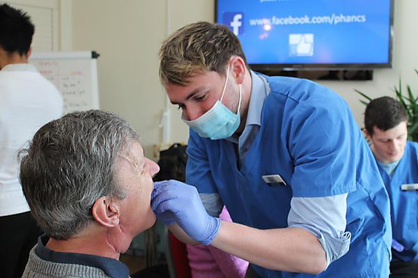 A dental student applies a fluoride varnish for a patient with head and neck cancer