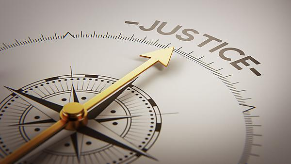 Compass with needle pointing towards the phrase 'Justice'