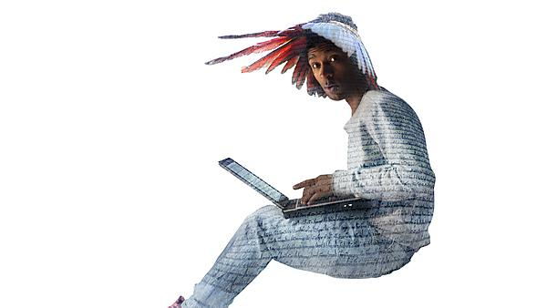 Plymouth Literature Project campaign image. Man sitting with a laptop, feathered headress