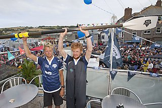 Tom and Lawrence raise one of the oars which rowed them to victory