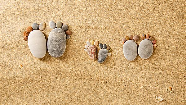 Pebbles on a beach, arranged in the shape of three sets of footprints. Image courtesy of Shutterstock (209141077).
