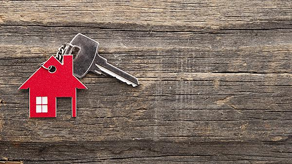 Door key attached to a key ring shaped like a red house, with a bleached wood background. Image courtesy of Shutterstock (227591032).