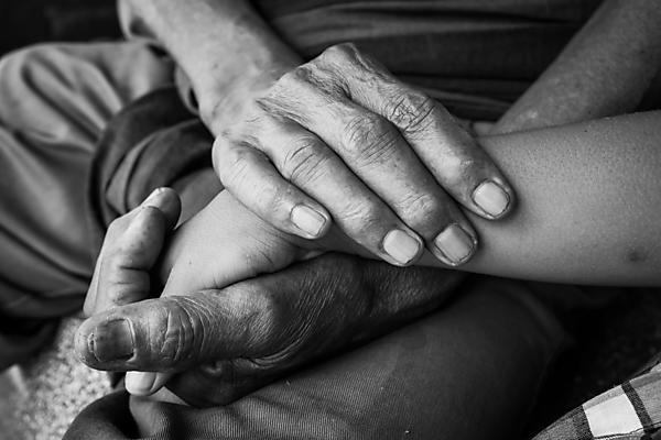 Black and white image of older man holding a young boy's hand. Image courtesy of Shutterstock (290072948).