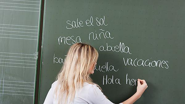 Teenage girl writing on blackboard in classroom [shutterstock_147463034]